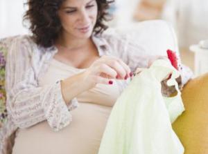 Беременная женщина шьет